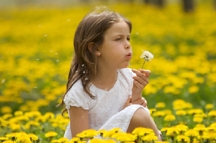 Child blowing on flower with allergy